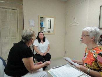 Juana Pecunia, (at left) speaks through her interpreter, Glenda Wagner, as her doctor listens.
