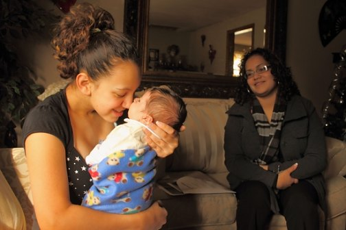 Yanisha Claudio, 15, cuddles her son, Jordan. Jennifer Colon of the Nurturing Families Network looks on.