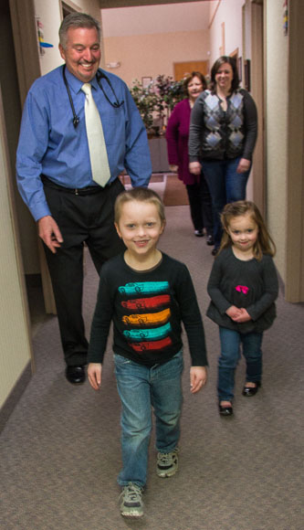 Dr. David R. Howlett follows two of his younger patients, Carter Pochron 4, and sister Haylee, 3, down the hall.