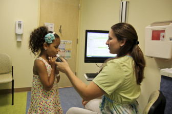 Megan Judkins, a nurse, helps Ariana Gomez, 7, test her breathing.
