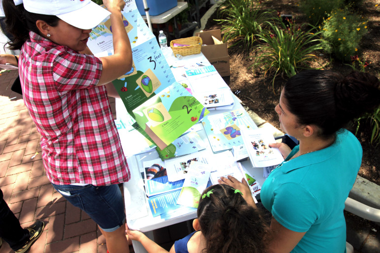 Elizabeth Quinonez shows off early childhood developmental charts with parents at the Danbury Farmers' Market in July. Quinonez, the community coordinator for Danbury's Promise for Children Partnership, has recruited about 20 parents who speak English and Spanish to spread the word about the programs.