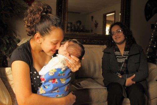 Yanisha Claudio, 15, cuddles her son, Jordan. Jennifer Colon of the Nurturing Families Network looks on.